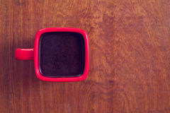 A red cup of coffee on wooden table. Royalty Free Stock Images