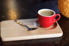 Red cup of coffee on wooden tray. Under light stock photos