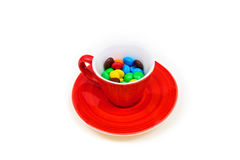 Red cup with colorful button-shaped chocolates. Royalty Free Stock Photography