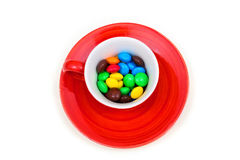 Red cup with colorful button-shaped chocolates. Royalty Free Stock Photos