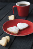Red cup and cookie hearts on a black background Royalty Free Stock Image