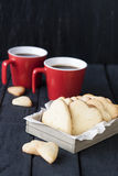 Red cup and cookie hearts on a black background Stock Images