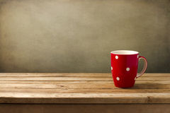 Red cup with dots. On wooden table over grunge background royalty free stock images