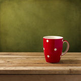 Red cup with dots. On wooden table over grunge green background royalty free stock photos