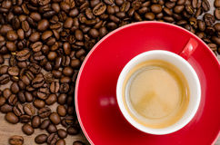Red cup of espresso with brown coffee beans. On a dark wooden table Royalty Free Stock Image