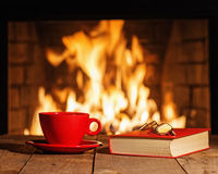Red cup, glasses and old book near fireplace on wooden table. Royalty Free Stock Photo