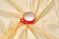 Red cup at the golden fabric drapery Royalty Free Stock Photos