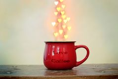 Red cup and heart shaped bokeh over it on white background. Love coffee concept.  royalty free stock photography