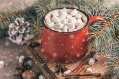 Red cup of hot cocoa with marshmallow. On the wooden cutting board with Christmas decorations and snow effect. Horizontal view. Close up stock images