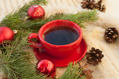А red cup of hot coffee, fir twigs, cones and Christmas-tree decorations on a white fur surface Royalty Free Stock Photography