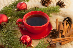 А a red cup of hot coffee, fir twigs, cones, cinnamon sticks and Christmas-tree decorations on a white fur surface Royalty Free Stock Photos