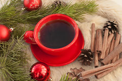 А red cup of hot coffee, fir twigs, cones, cinnamon sticks and Christmas-tree decorations on a white fur surface Royalty Free Stock Photography