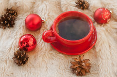 A red cup of hot coffee, fir twigs, cones, cinnamon sticks and Christmas tree decorations on a white fur surface Stock Image
