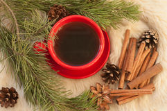 А a red cup of hot coffee, fir twigs, cones, cinnamon sticks and Christmas-tree decorations on a white fur surface Stock Photos