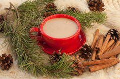 А a red cup of hot coffee, fir twigs, cones, cinnamon sticks and Christmas-tree decorations on a white fur surface Stock Photo