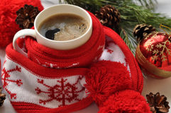 A  red cup of hot coffee, a red and white knitted scarf with pompons, a fir twig, cones and Christmas-tree decorations Stock Images