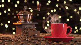Red cup of hot coffee with smoke and coffee grinder stock footage