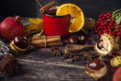 Red cup of hot mulled wine in autumn among leaves. Cup of warm mulled wine on wooden table with slice of orange in clove Stock Image