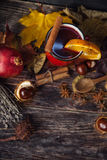 Red cup of hot mulled wine in autumn among leaves stock image