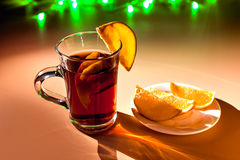 Red cup of hot mulled wine with orange slices. Green garland. Stock Image