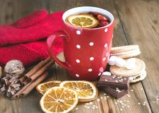 Red cup of hot tea with orange and berries Christmas winter beverage Christmas food concept Wooden background Cinnamone sticks Coo. Kies Mittens stock image