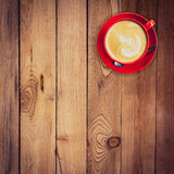 Red cup and latte coffee on wood table. Stock Image