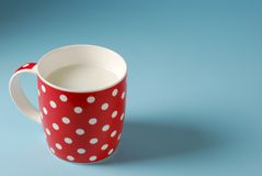 Red cup of milk on a blue background Stock Photos