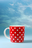 Red cup over beautiful blue sky background. With copy space Royalty Free Stock Photography
