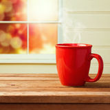 Red cup over window. On a wooden table Royalty Free Stock Images