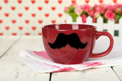 Red cup with paper mustache on a colorful background Royalty Free Stock Photography