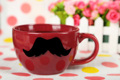 Red cup with paper mustache on colorful background. Stock Photo