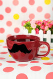 Red cup with paper mustache on colorful background. Royalty Free Stock Photography