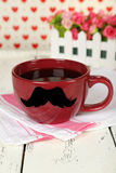 Red cup with paper mustache on white wooden background Stock Photography