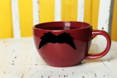 Red cup with paper mustache on white wooden background Stock Image