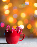 Red cup, red mug with candy canes in snow with bokeh in the background stock photo