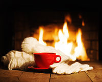 Red cup scarf, gloves and cap on wooden table near fireplace. Stock Image