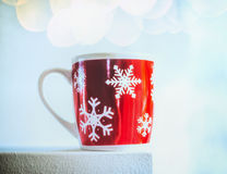 Red cup with snowflakes and bokeh on light blue winter day background Stock Photography