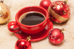 A a red cup of strong black coffee and bright red and golden fir balls on a fur surface Royalty Free Stock Image
