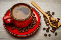 A red cup of tasty coffee with coffee beans, on wooden backgroun Royalty Free Stock Photos
