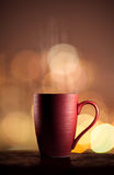 Red cup of tea with beautiful city bokeh Royalty Free Stock Image