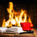 Red cup of tea or coffee, magnifier glass and old books. royalty free stock images