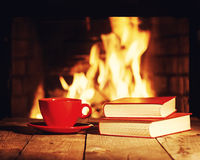 Red cup of tea or coffee and old books near fireplace. Stock Images