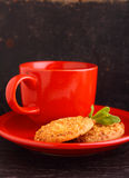 Red cup with tea and cookies. On a black background Royalty Free Stock Photos