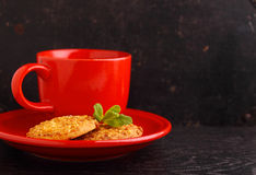 Red cup with tea and cookies. On a black background Stock Photos