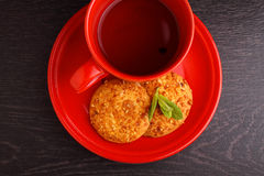 Red cup with tea and cookies. On a black background Stock Images