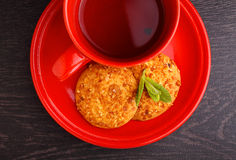 Red cup with tea and cookies. On a black background Royalty Free Stock Image