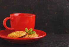Red cup with tea and cookies. On a black background Stock Photo