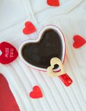 Red cup of tea in the form of heart with a biscuit Stock Image
