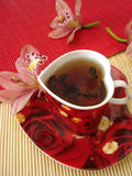 Red cup of tea in the form of heart with pink orchids over straw. Matt Royalty Free Stock Image