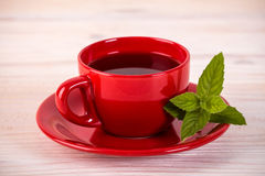 Red cup of tea with green leaves. On wooden table stock images